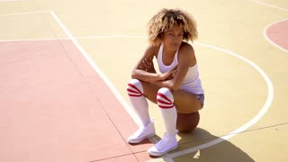 Attractive female athlete sits on basketball