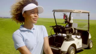 Attractive female golfer with a golf cart