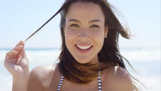 Attractive friendly young brunette woman with a lovely warm smile sitting on a tropical beach with her hair blowing in the wind close up view