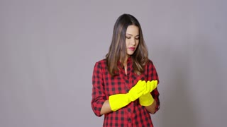 Attractive housewife holding up gloved hands in colorful yellow rubber gloves with a wry smile as she prepares to do the housework