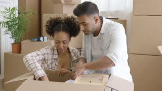 Attractive mixed race couple sitting on the floor with opened box and unpacking their things in new home. Girl holding frame with photo.
