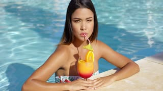Attractive serious young woman standing in the water at the edge of a pool sipping an orange rum cocktail while on summer vacation