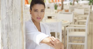 Attractive single young woman in white robe sitting near wooden patio with dining tables and chairs outdoors