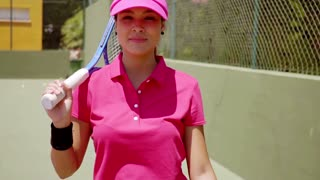 Attractive smiling tennis player holding racket against her shoulder and wearing bright pink shirt and visor while standing next to green wall