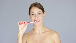 Attractive smiling young woman with bare shoulders brushing her teeth with a plastic toothbrush in a concept of oral and dental hygiene