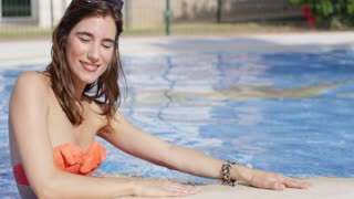 Attractive trendy young woman with her sunglasses on top of her head in a swimming pool leaning against the edge smiling at the camera