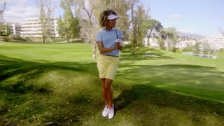 Attractive woman golfer walking on the course