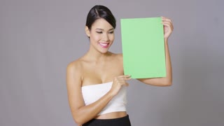 Attractive woman in a white summer tube top standing holding a blank green sign looking at it with a smile