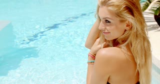 Attractive woman in the pool smiles at camera