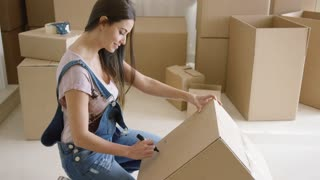 Attractive woman moving house and packing her personal belongings into cardboard boxes writing the contents on the lid