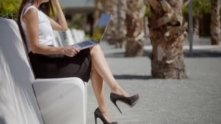 Attractive woman sitting on a bench with a laptop