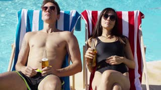 Attractive young couple enjoying a beer while relaxing in their swimsuits on deck chairs near a pool toasting each other with the bottles