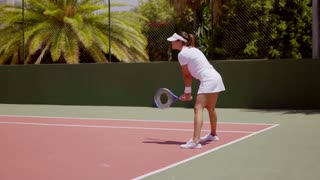Attractive young female tennis player standing ready to receive service on an outdoor all weather tennis court