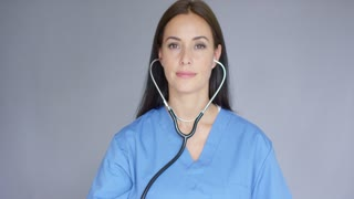 Attractive young nurse or female doctor holding up a stethoscope with the disc to the camera with a serious expression head and shoulders on grey