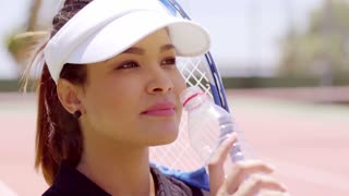 Attractive young tennis player drinking bottled water close up head shot on an all weather court