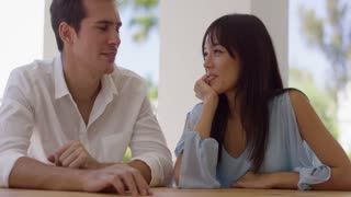 Attractive young white and Asian couple on a date sitting close to each other at table outside