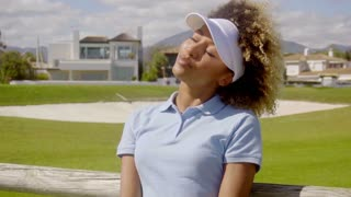 Attractive young woman golfer relaxing