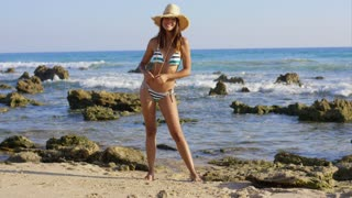 Attractive young woman in a bikini and straw sunhat walking on a beach on a rocky shoreline smiling with pleasure in evening light