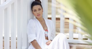 Attractive young woman in white robe over bathing suit with calm expression sitting near fence outdoors