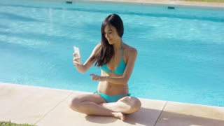 Attractive young woman posing for a selfie in her bikini sitting cross-legged on the tiled surround of a swimming pool