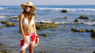 Attractive young woman posing in a bikini and sarong on a rocky seashore holding her sunhat in the sea breeze looking at the camera