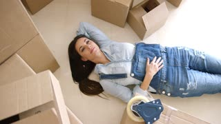 Attractive young woman relaxing on her back on the floor surrounded by brown cardboard cartons as she packs up the house for a move or renovation.