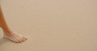 Bare Feet Coated in Sand Walking on Beach
