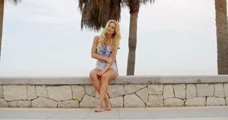 Barefoot Woman Sitting on Stone Wall at Beach