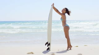 Bathing beauty holds surfboard and smiles at camera while standing on tip toes near the ocean