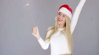 Beautiful adorable girl having fun with chrismas sparkler. She wearing Santa Claus hat and white woolen sweater.