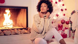 Beautiful african american woman with big afro haircut seated next to fireplace and white christmas tree with presents under it
