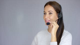 Beautiful and positive female call center agent at work. She speaking with customer using headset. Smiling. Isolated on gray background.