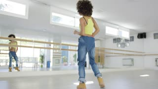Beautiful and sexy female african american dancer shows her skills in studio. She wearing heavy work boots and baggy jeans. Smiling to the camera