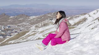 Beautiful asian girl sitting at the snow in hight mountains. She wearing snowboard clothes. Looking with smile to the camera.