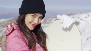 Beautiful asian girl standing on ski slope with her snowboard. She looking to the camera. Wearing pink ski jacket and black hat.