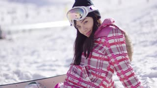 Beautiful asian snowboarder sitting on snow and relaxing. She looking into camera direction with smile. Wearing pink outfit and goggles.