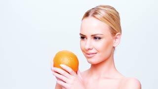 Beautiful Blond Girl Holding Orange Fruit While Isolated