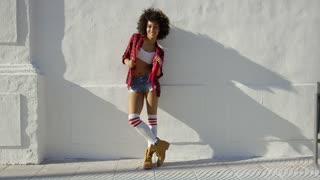 Beautiful fashionable african american girl leaning against white concrete wall. She wearing work boots very short jeans checkered shirt. impressive afro haircut. Looking at camera and smiling.