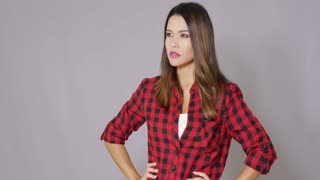 Beautiful female construction worker using measure tape. She wearing red checkered shirt. Isolated on gray background.