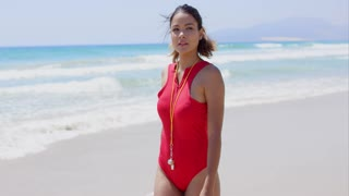 Beautiful lifeguard walking near surf on sunny day while wearing red swim suit