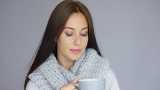 Beautiful long haired, brunette woman holding in her hand cup of hot drink. She wearing woolen scarf around her neck. She trying to warm up herself. Isolated on gray background.