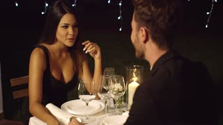 Beautiful long haired woman has dinner with man at fancy restaurant with white table setting and a lone candle