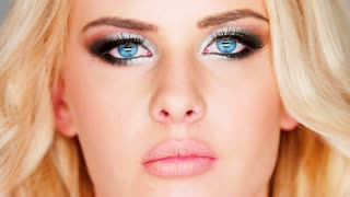 Beautiful pensive blue-eyed blond woman with heavy modern creative eye makeup biting her lip in a sensual gesture