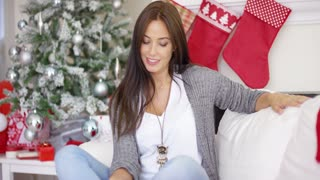 Beautiful relaxed young woman celebrating Christmas with a happy smile as she sits on a sofa in her festive decorated living room