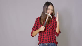 Beautiful sexy girl making faces and have fun with hammer tool. She wearing checkered shirt and jeans. She smiling to the camera while isolated on gray background.