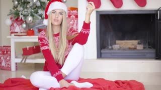 Beautiful sexy girl sitting on the floor next to Christmas tree and fireplace at her living room. She wearing Santa Claus hat white leggings and winter woolen sweater. Smiling