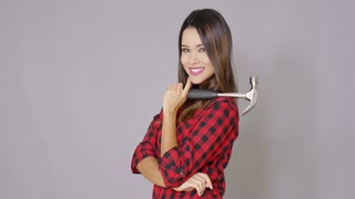 Beautiful sexy girl wearing checkered work wear shirt. She posing with hammer tool and smiling to the camera. Isolated on gray background.