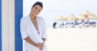 Beautiful single woman in white robe with cheerful expression standing outdoors near beach house and beachgoers