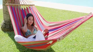 Beautiful single young adult woman in bikini top and white pants seated comfortably in colorful hammock near swimming pool reading a book