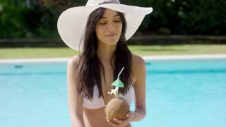 Beautiful woman in an elegant white straw hat sitting near a swimming pool sipping a coconut cocktail from the husk with a smile